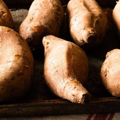 Cooked sweet potatoes lined up on a cookie sheet