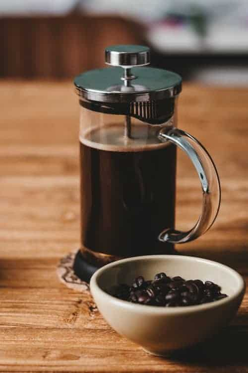 French press coffee with coffee beans on a wooden table