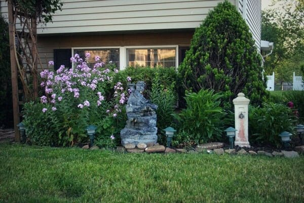 After photo of freshly trimmed shrubs and bushes and edged flower bed in a front yard DIY curb appeal property makeover