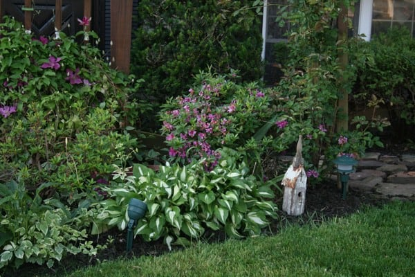 Flower bed after wedding, edging, and mulching with some simple yard decor including a small wooden church as part of a curb appeal makeover on a budget