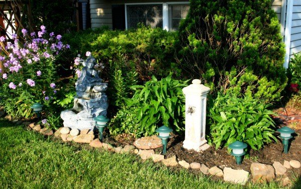 Front yard flower bed after photo with fresh mulch, edged, stones being used for edging, new in-ground lighting and more - DIY curb appeal makeover