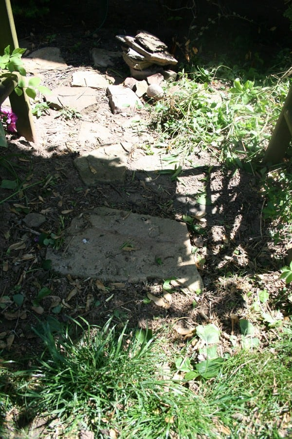 Small garden path under arbor being reset into place using sand as part of a DIY curb appeal makeover