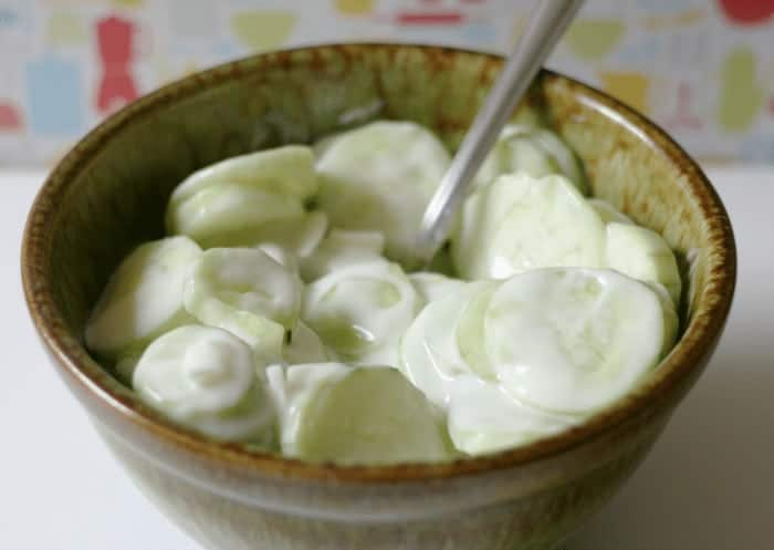 Vintage green bowl filled with creamy cucumbers - a wonderful summer party recipe