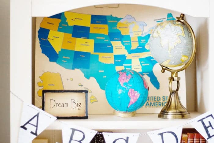 School room bookshelf with a DIY globe made from a thrift store white glass light globe in the center, a map of the United States in the Back, vintage encyclopedias on the shelf below and the encouraging sign, Dream Big to the left on the shelf with an ABC alphabet pennant strung across the shelf bottom