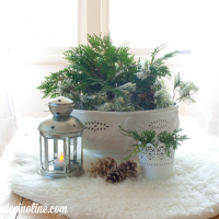 Christmas coffee table with greens, lantern, fur throw and pine cones from cupcakesandcrinoline.com