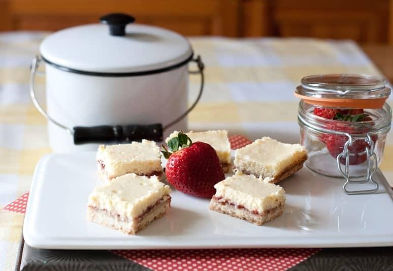 Strawberry and Lemon Shortbread Cheesecake Bars on plate from cupcakesandcrinoline.com