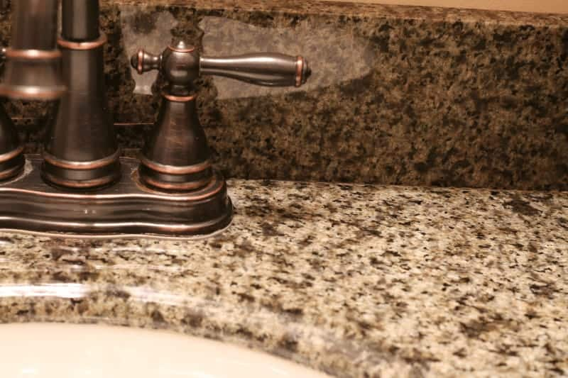 First pass with Zep for removing lime deposits, water stains, and hard water deposits from granite countertop in bathroom