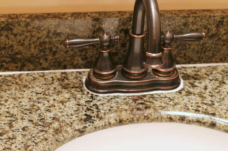 Cleaning product on granite countertop used to remove water stains and hard water deposits safely from granite