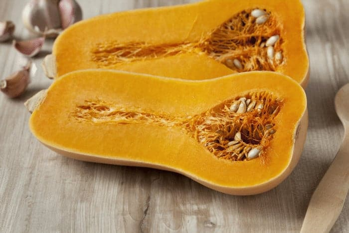 Butternut squash cut in half with seeds on cutting board