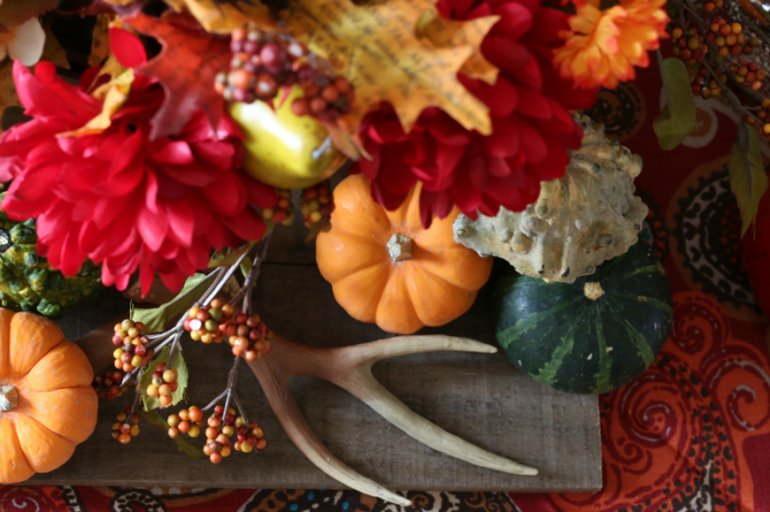 Close up of Thanksgiving Tablescape with pumpkins, gourds adn antlers one at cupcakesandcrinoline.com