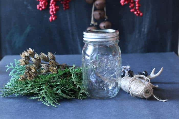 Create your own rustic holiday decor with a mason jar, fresh cut greenery, a mason jar, Christmas potpourri and twine.  Get the details at:  www.cupcakesandcrinoline.com.