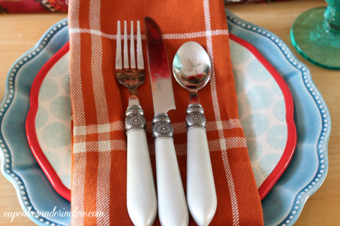 Tablescape with Pioneer Woman dishes, silverware and glassware with plaid napkins via cupcakesandcrinoline.com