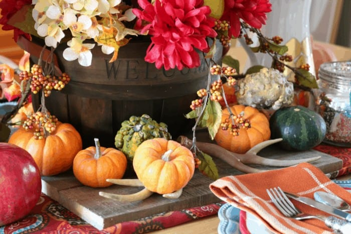 Thanksgiving centerpiece and tablescape with mini pumpkins, pomegranate, antlers, gourds and Pioneer Woman dishes and silverware - cupcakesandcrinoline.com