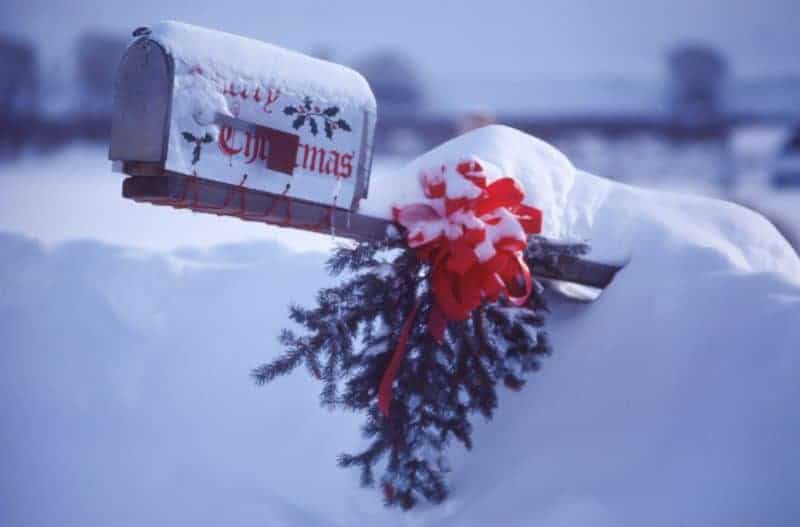 How to make a bow - large red ribbon on evergreen bough attached to mailbox post buried in snow