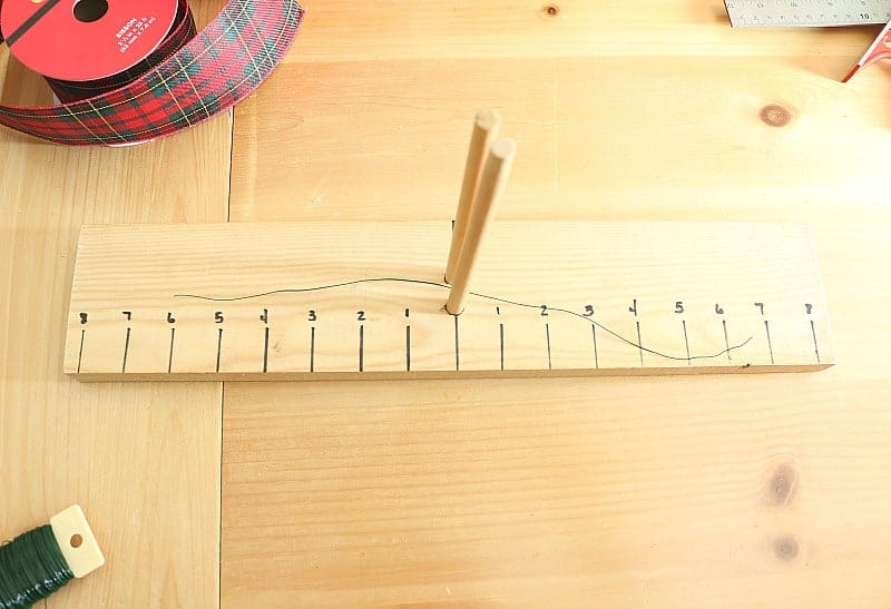How to make a bow maker board - dowels in center of board with 1 inch increments marked and wire placed between dowels to start making a bow