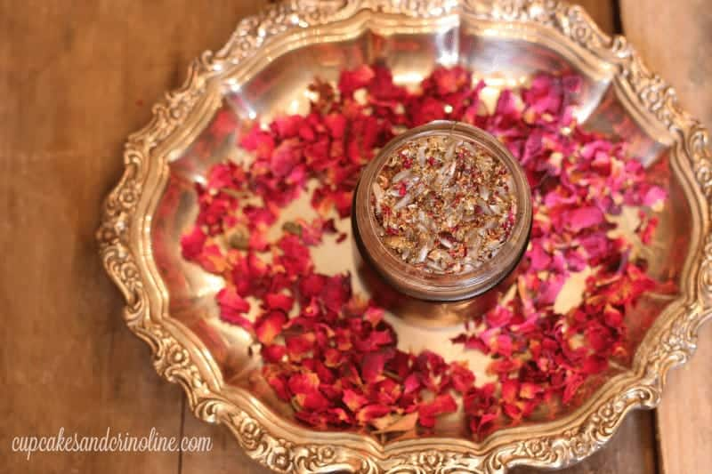 Dried rose petals scattered on an antique silver platter with homemade face scrub in a glass jar.