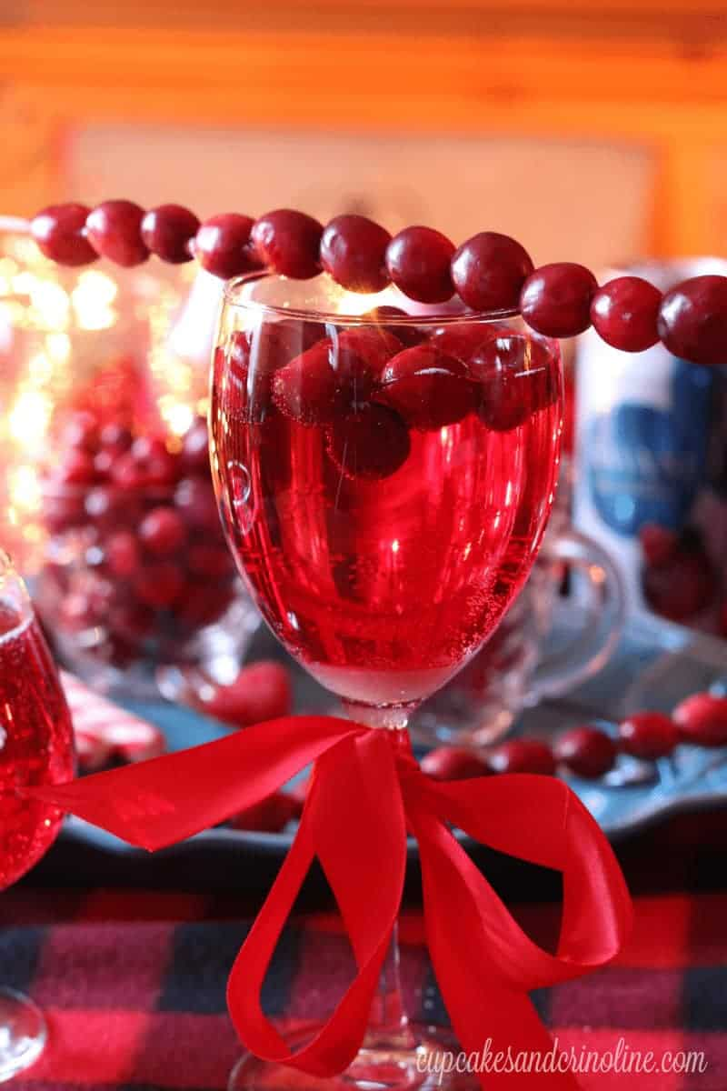 Holiday drinks made easy! A row of cranberries atop a wine glass filled with a cranberry sparkler.