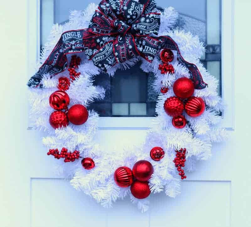 white Christmas wreath with clusters of red ornaments attached and a black, red, and white Christmas ribbon