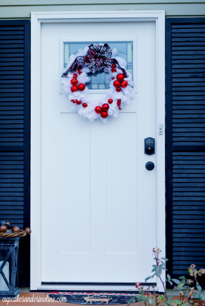 White front door with black shutter, white Christmas wreath, red ornaments and black, red and white ribbon at cupcakesandcrinoline.com