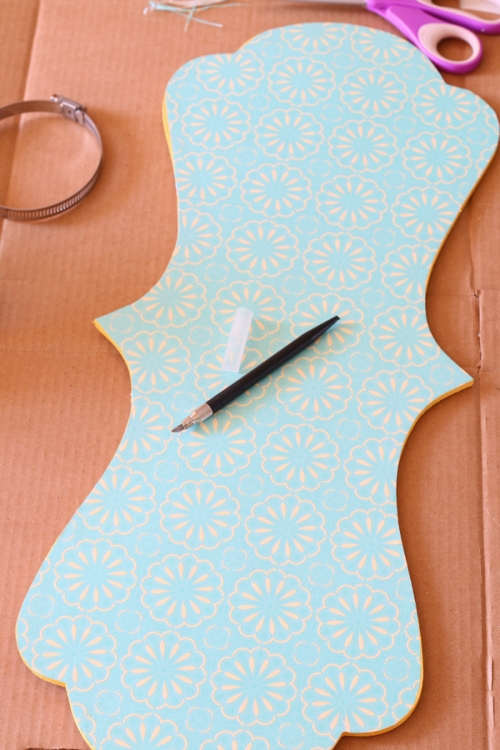 Use Exacto to trim edge of adhesive paper even with edge of wooden plaque
