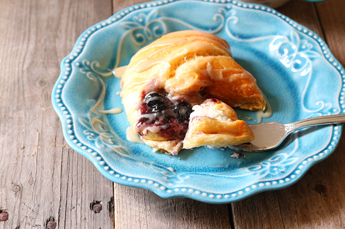 Easy Blueberry Cheese Danish on plate with icing and fork