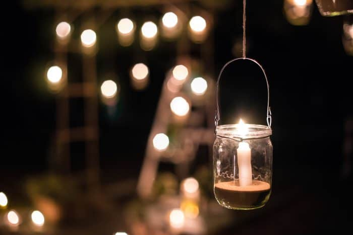 Globe lights strung from trees and a mason jar candle holder