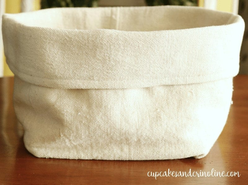DIY collapsible storage bin made from fabric, a dropcloth in this case! So inexpensive and easy to make with basic sewing skills - from cupcakesandcrinoline.com