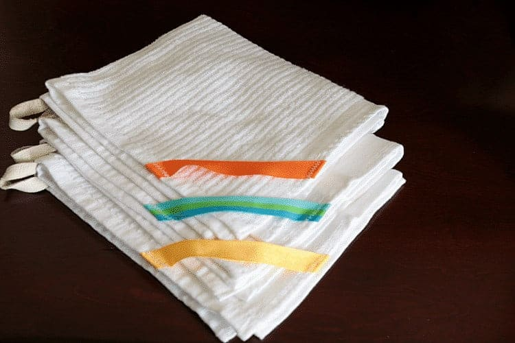 Simple Hanging Dish Towel - stack of three white, one with orange trim, one with yellow trim, and one with green and blue trim