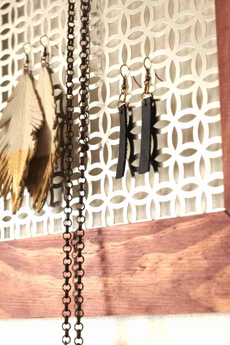DIY leather earrings and white feather earrings dipped in gold and black leather dangle drop earrings. Get the tutorial at www.cupcakesandcrinoline.com