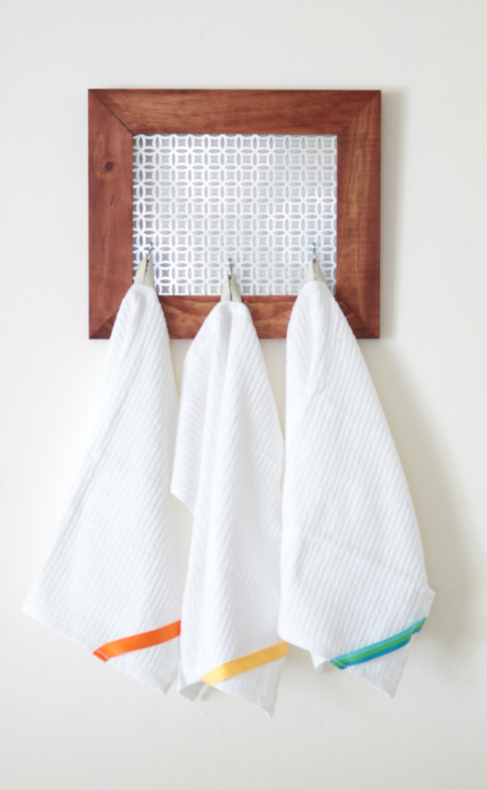 DIY color-coded cleaning towels hanging from a DIY farmhouse style wall organizer.
