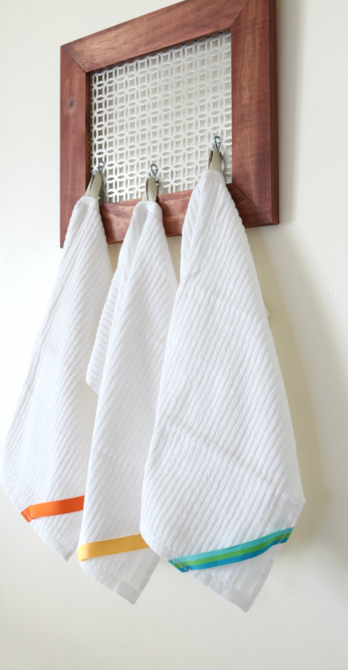 Color-coded cleaning towels with leather loops shown hanging from a DIY farmhouse-style wood and metal hanging organizer. www.cupcakesandcrinoline.com