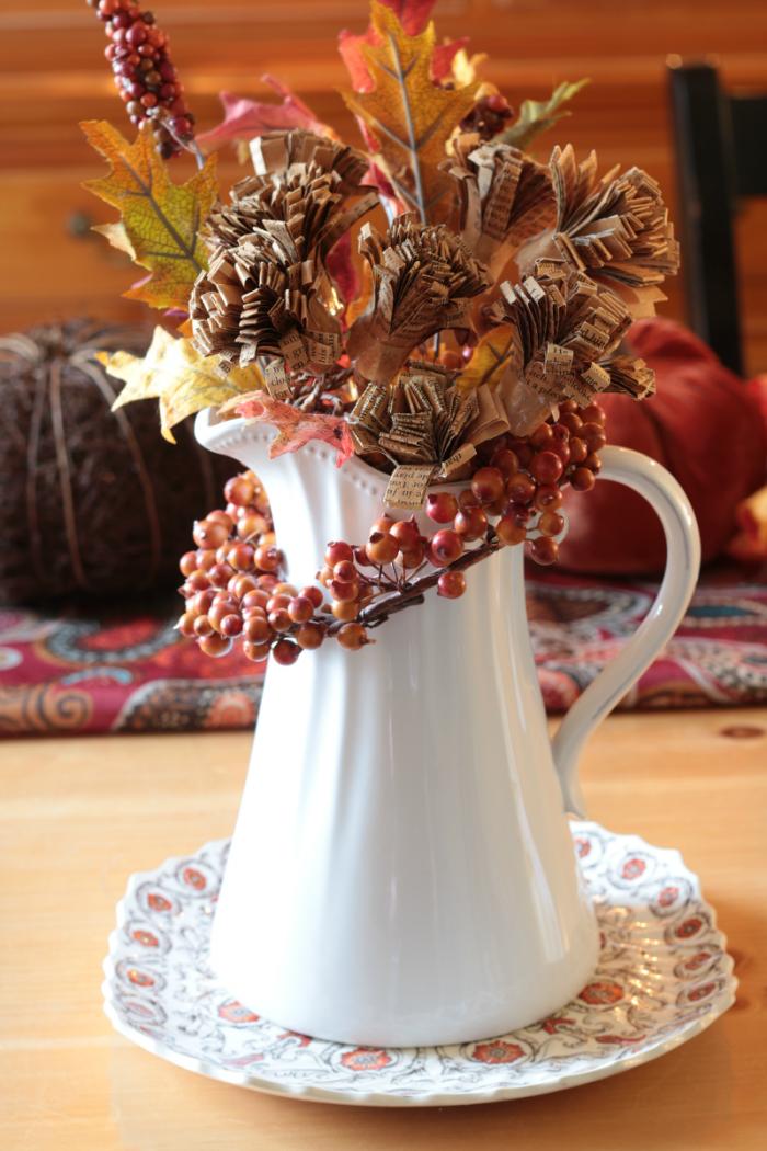 White ironstone pitcher filled with book page flowers and faux leaves placed atop an antique Spode plate. Autumn Decor 2016 www.cupcakesandcrinoline.com