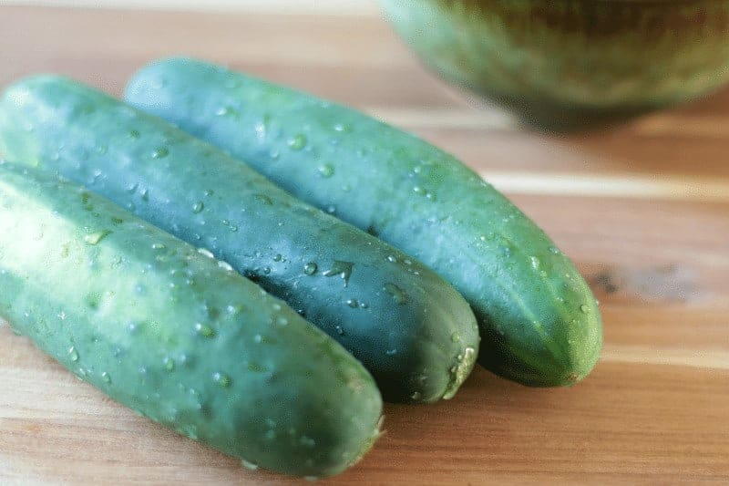 Three fresh cucumbers on a cutting board - main ingredient for a creamy cucumber salad