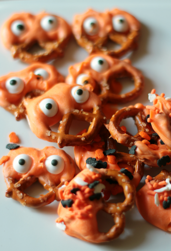 Googly eyed candy dipped pretzels and candy-coated Halloween Oreos - Halloween Snacks at www.cupcakesandcrinoline.com