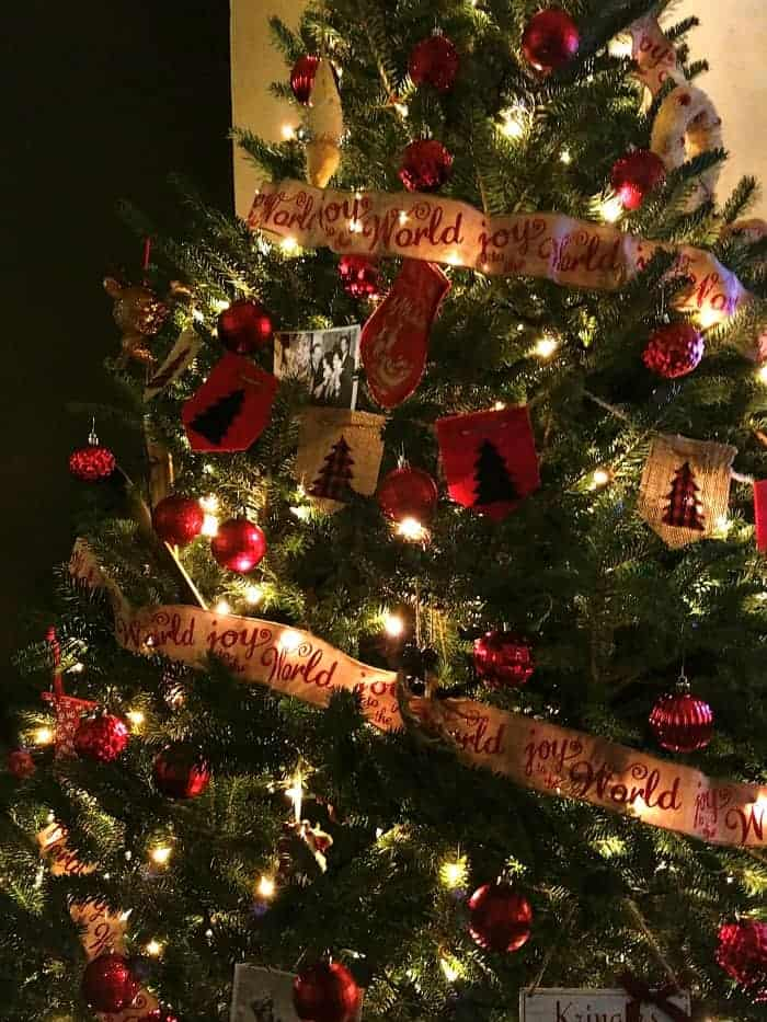 fresh-cut-christmas-tree-at-night-dressed-in-red-ornaments-and-joy-to-the-world-burlap-glitter-garland