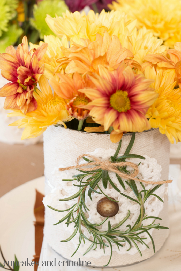 Upcycled tin can table decor. Cover tin cans in drop cloth scraps, add doilies, lace and ribbon and fill with fresh flowers for a beautiful, elegant yet rustic table setting. Perfect for Thanksgiving, weddings and showers. Get the details and more inspiration at www.cupcakesandcrinoline.com