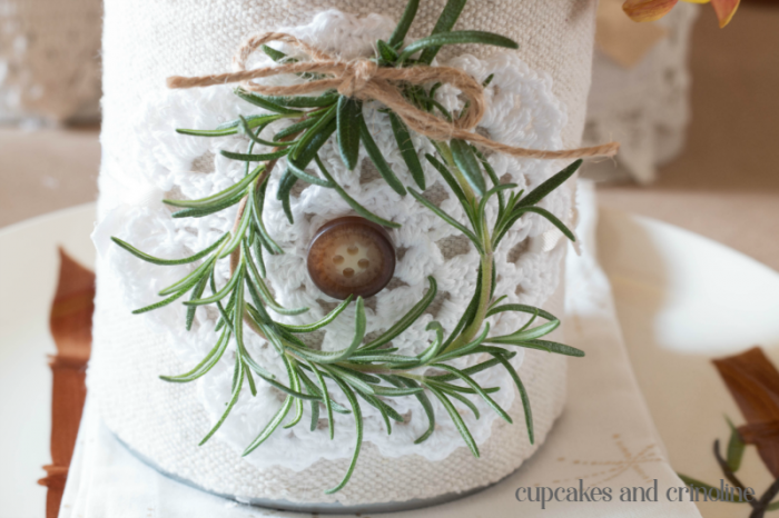Upcycled tin can table decor, rustic and lovely. Cover can in drop cloth, add doilies, ribbon and a simple to make Rosemary sprig wreath. Table decor on a budget. Get the details and more inspiration at www.cupcakesandcrinoline.com