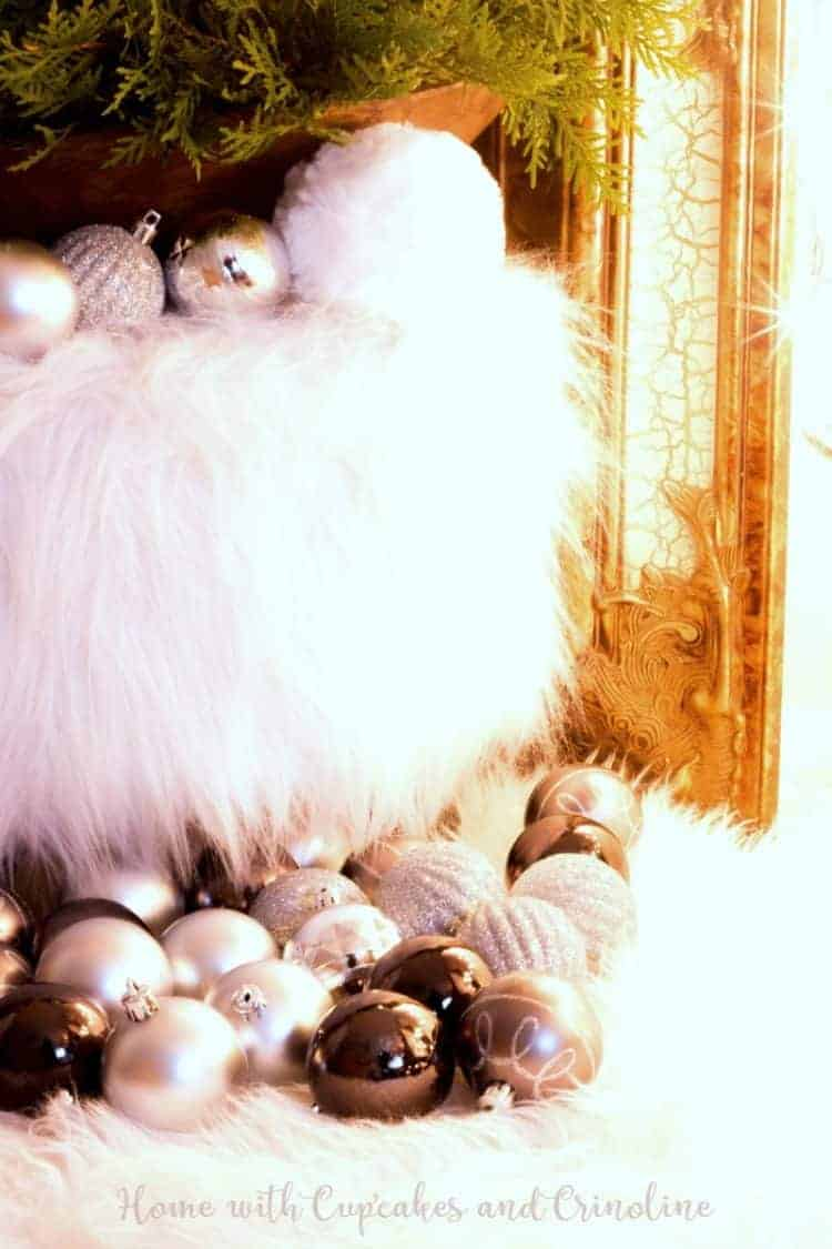 White faux fur carpet and stool with vintage dough bowl and ornaments.