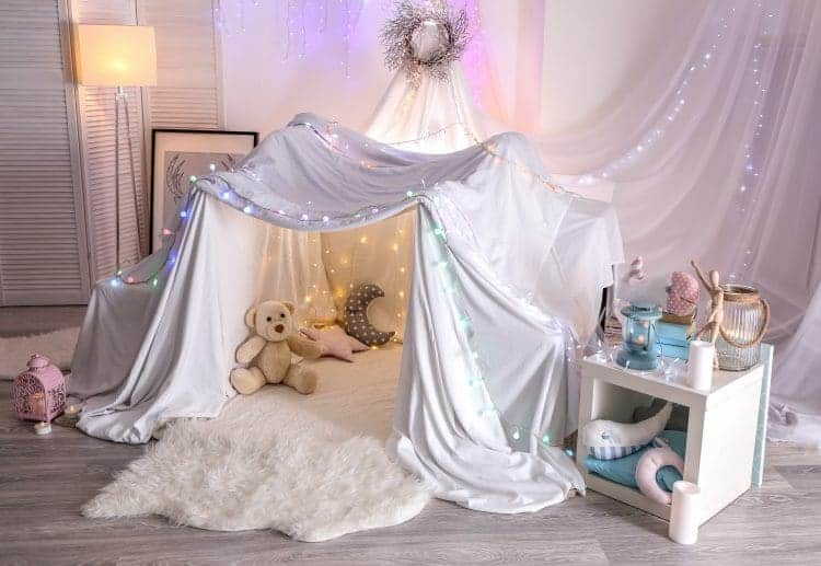 Set up a kid's tent in the living room using sheets and twinkle lights