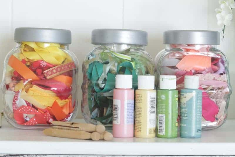 Ribbons in jars separated by color family, craft paints, and wooden clothespins