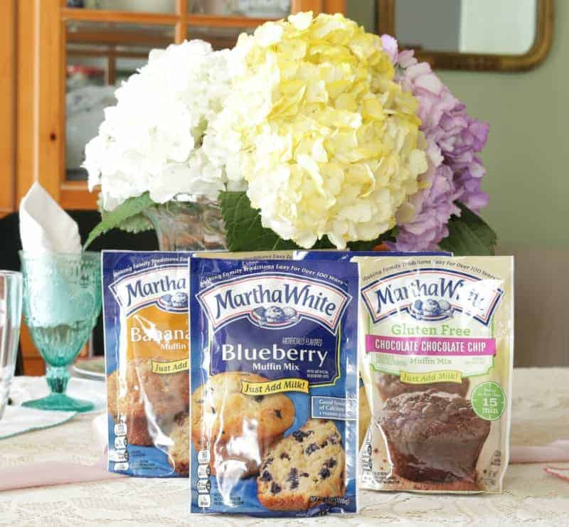 Fresh bouquet of cut hydrangeas in a vase on lace tablecloth with three bags of muffin mix