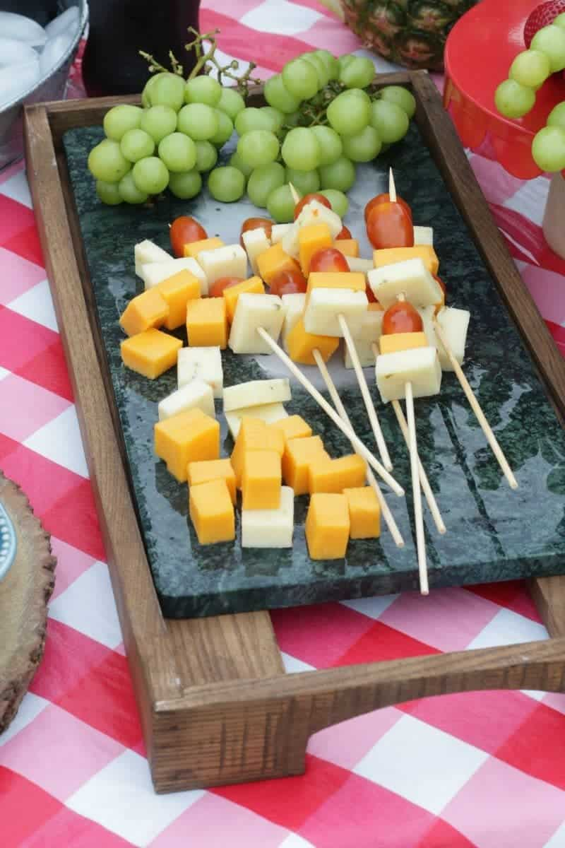 Cheese and tomato shish kabobs on a soapstone with fresh grapes and cheese cubes