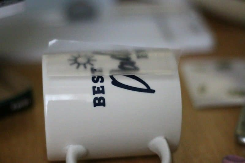 Once vinyl has properly adhered to mug begin to slowly remove the transfer tape, contact paper or laminate (whatever you used to transfer the cut) and rub down vinyl as needed.