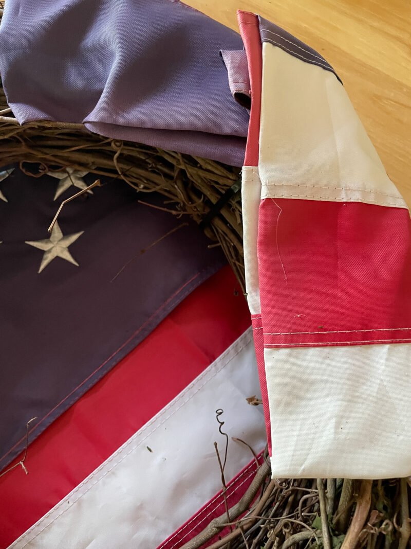 American Flag folded to back of a grapevine wreath and hot glued in place