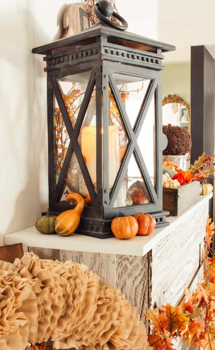 Close up of black lantern and fall decor on a fireplace mantel