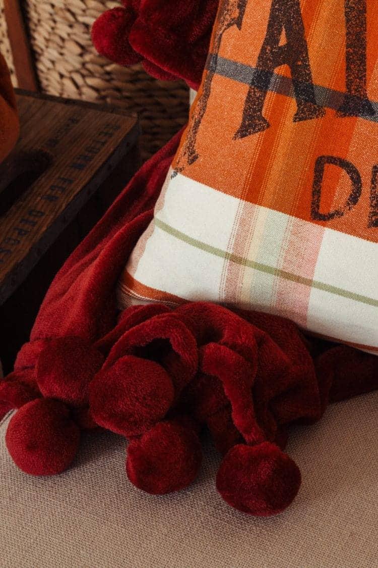 close of up cranberry colored plush throw with pom pom fringe