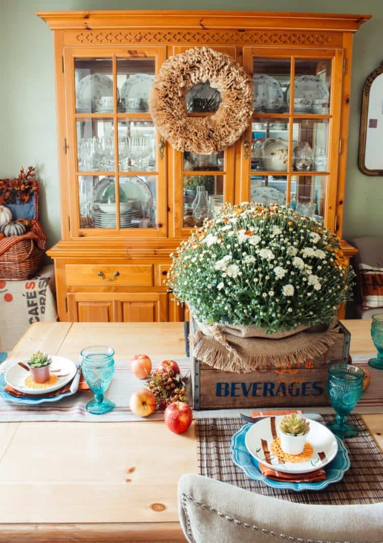 China cabinet with coffee filter wreath on it and fall tablescape