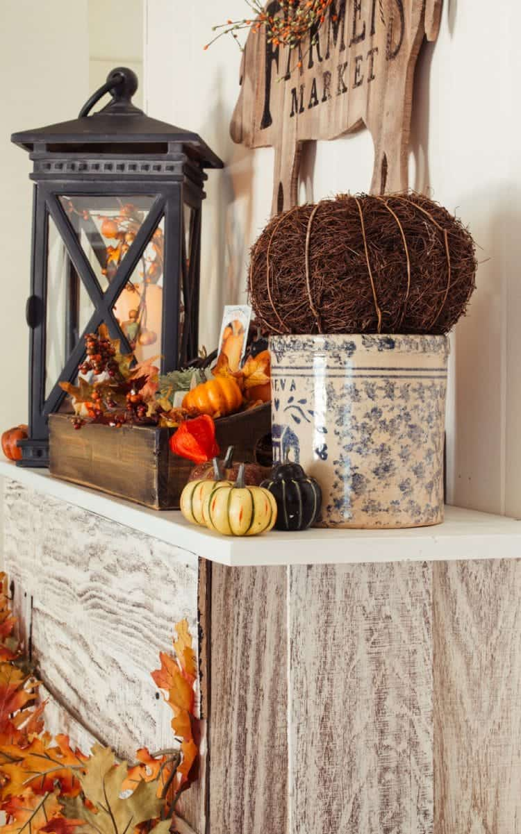 Autumn and fall decor on a faux fireplace mantle including pumpkins, a black lantern, and a fall leaf garland