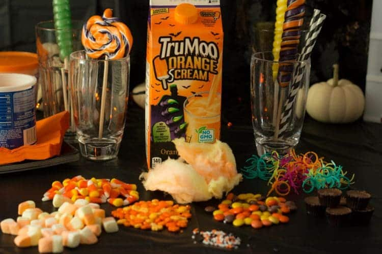 TruMoo Orange Scream - the perfect ingredient for a Halloween Inspired FreakShake! Orange Halloween FreakShake Milkshake ingredients with candy corns, M&M's, cotton candy, lollipop, and spider rings