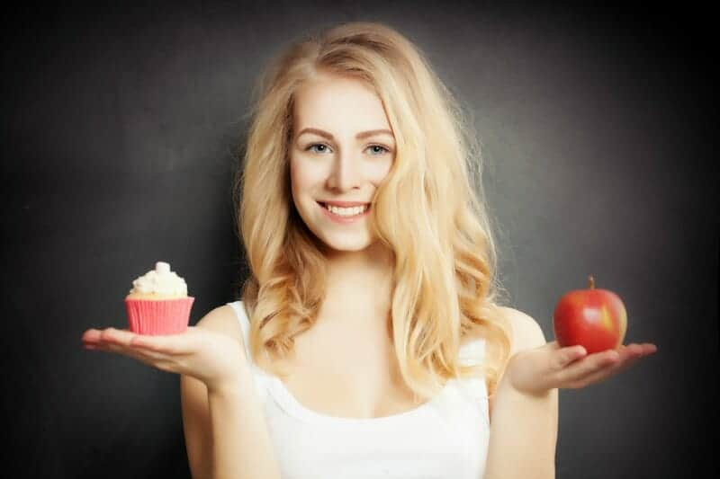 Blonde girl holding an apple and a cupcake
